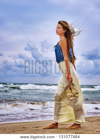 Summer girl sea.  Woman barefoot walking on coast and carry her shoes.
