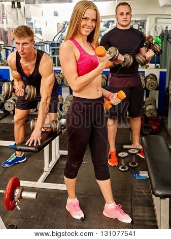 Group of people working with  dumbbells his body at gym. Slim girl in foreground.