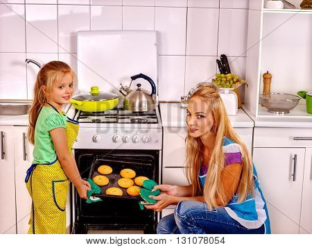 Mother and daughter bake cookies in oven into kitchen  at home.