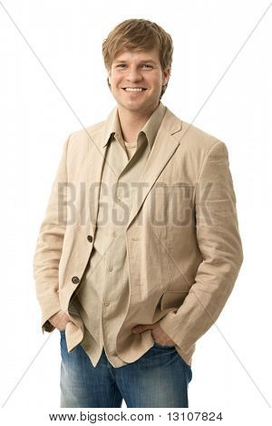 Portrait of casual young man, standing with hands in pocket, smiling. Isolated on white.?
