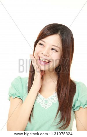 portrait of young Japanese woman pleased on white background
