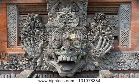 Hinduism: Statue decorated with a beautiful glowing flower in front of the Ubud Palace on Bali