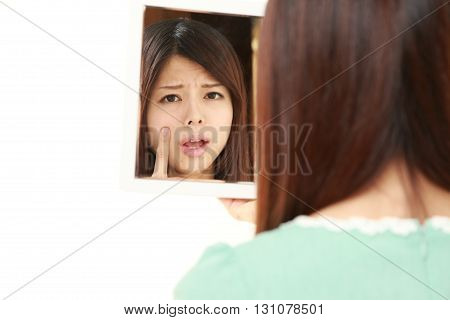 portrait of young Japanese woman worries about dry rough skin on white background