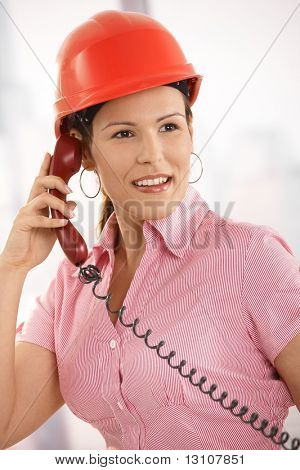 Closeup portrait of happy architect talking on landline phone in office, smiling.?