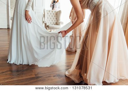 Bridesmaids Help To Wear A Wedding Dress