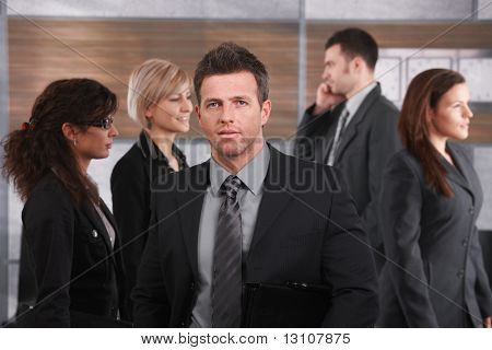 Portrait of businessman wearing grey suit, holding suitcase, standing in office lobby.?
