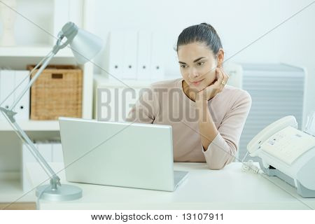 Attractive young woman sitting at desk, looking at laptop computer screen, thinking.