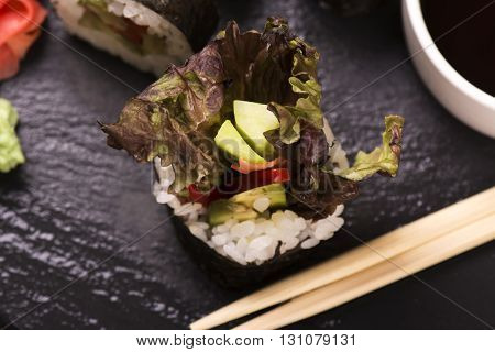 Assortment of sushi rolls with salmon and vegetables, served with soy sauce and chopsticks over grunge wooden background. Selective focus