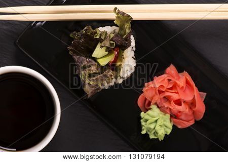 Vegetarian sushi roll served with wasabi, ginger and soy sauce over black stone background. Selective focus