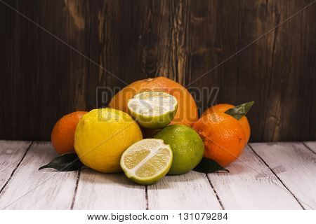 Pile of fresh citrus fruits over wooden background. Lemonade ingredients. Healthy drink concept. Toned image. Selective focus