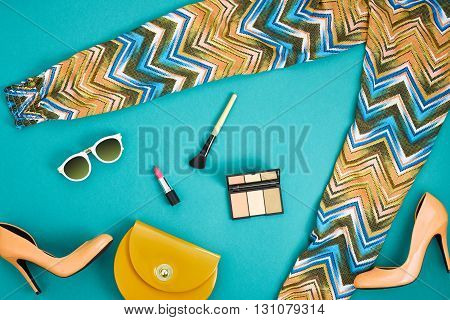 Urban summer girl colorful outfit. Fashion stylish clothes, cosmetics, makeup accessories. Stylish glamor heels, handbag clutch, trendy pants, sunglasses. Woman essentials. Unusual, top view