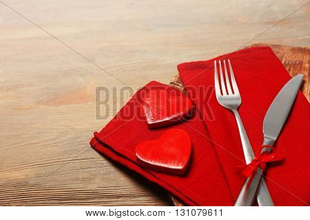 Composition of fork, knife, napkin and decorative hearts on cutting board, on wooden table background