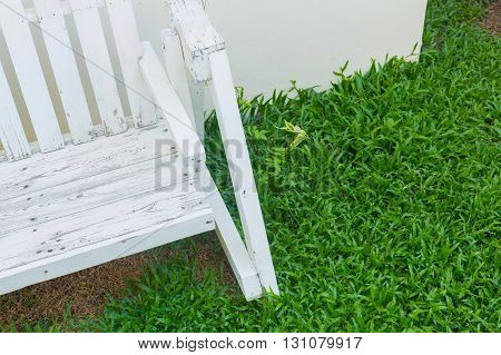 white wooden bench seat in green grass garden