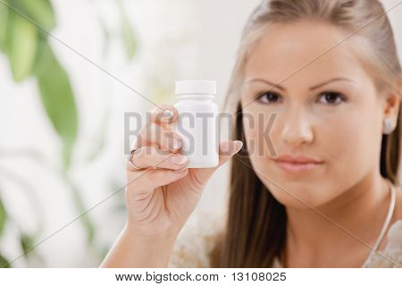 Beautiful young woman showing white pill bottle, copy space.