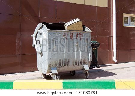 Beige suitcase thrown in a metal trash can standing against a wall covered with brown tiles. In the foreground is the curb yellow and green colors.