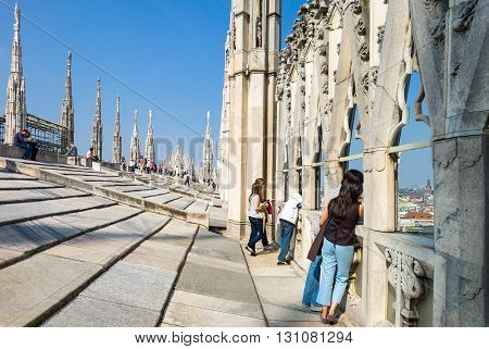 Milan Italy - April 21 2011: People between the spires and marle works of the Duomo cathedral rooftop