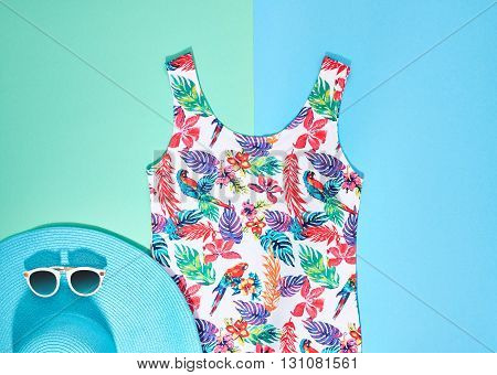 Beach.Beach background.Summer girl clothes set, accessories.Beach minimal style. Fashion colorful dress, stylish blue beach hat, and trendy necklace, sunglasses.Unusual overhead beach outfit, top view