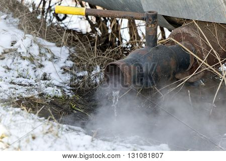 Hot water with steam flows from a rusty crane in winter
