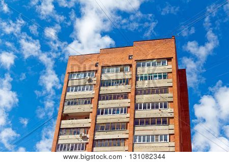 Red multi-storey building with wires on the background of blue sky with clouds