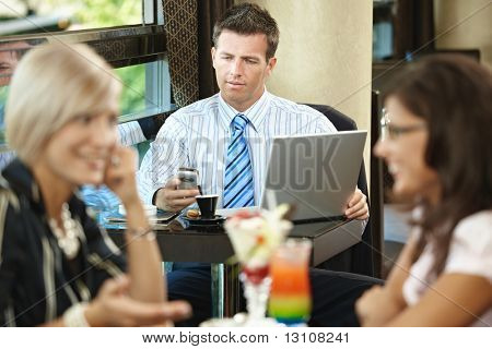 Businessman using laptop and mobile in cafe, young woman eating sweets and talking in the foreground. Selective focus on businessman.