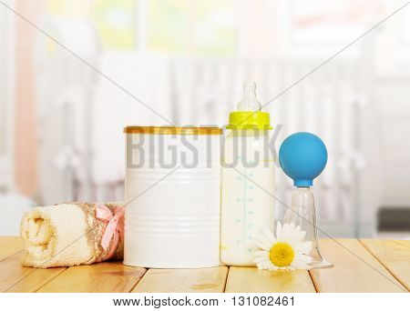 Bank of powdered milk, bottle, manual breast pump and a towel on the background of the kitchen.