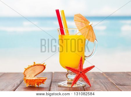 Orange cocktail, starfish and shell-casket with a pearl on a background of blue sea.