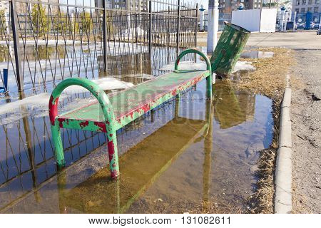 Metal bench and a metal rubbish bin standing in water from melting snow