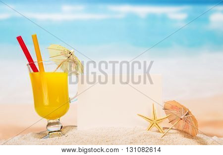 Blank card, a glass of orange cocktail and starfish in the sand against the sea.