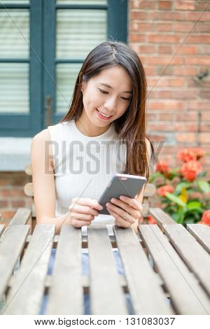 Woman using mobile phone at outdoor cafe