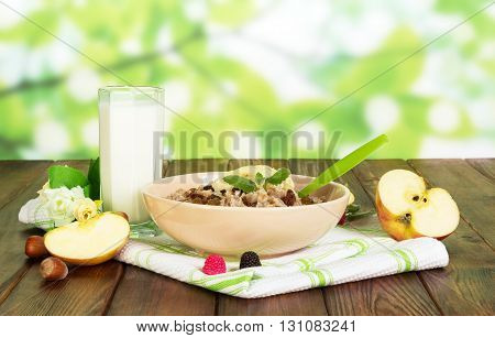 A bowl of oatmeal, a cup of yogurt, fruits and nuts on abstract green background.