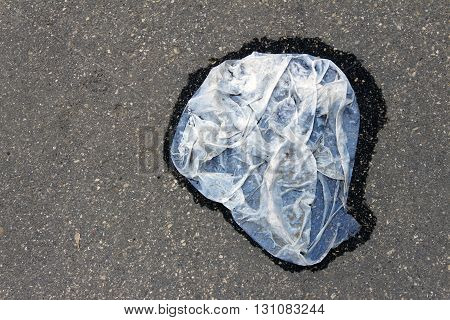 Wet and dirty plastic bag lying on dry pavement