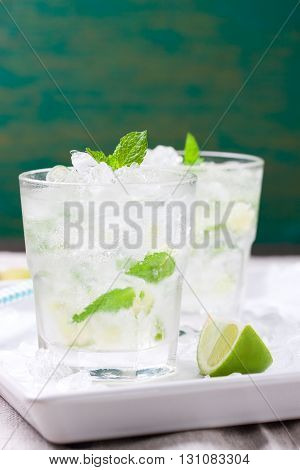Non alcohol cold mojito cocktail with fresh lime mint and crushed ice on a white plate closeup