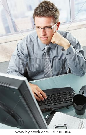 Handsome mid-adult businessman deep in thought concentrating on computer work looking at screen sitting at office desk.?