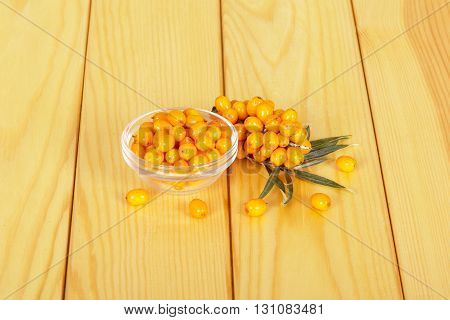 A bowl with berries of sea buckthorn and bunch on a background of light wood.