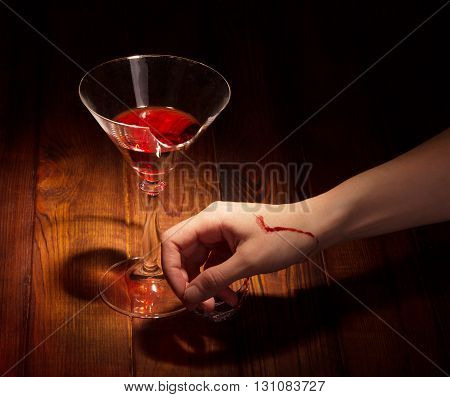 Broken glass of wine and chopped hand against the dark wood.
