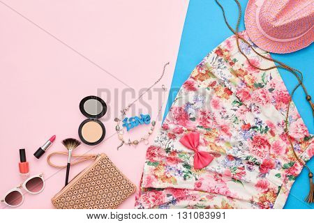 Fashion summer girl clothes accessories set. Woman essentials. Cosmetics, makeup. Stylish beige handbag clutch, trendy dress, hat, necklace, sunglasses . Unusual overhead outfit, top view on pink