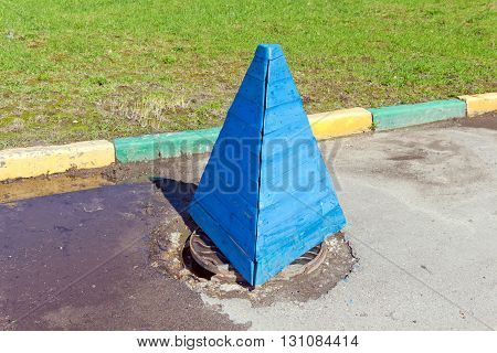 Blue wooden safety cone stands on a sewer manhole