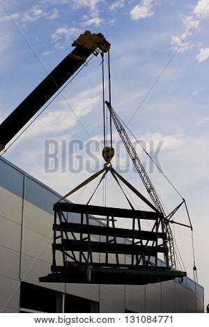 A crane rising some construction equipment as a construction concept
