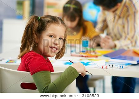 Portrait of happy elementary age child sitting at desk looking at camera in art class in primary school classroom, smiling.?