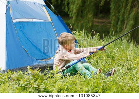 Cute Small Boy Sits Near A Tent With A Fishing Rod In His Hands.