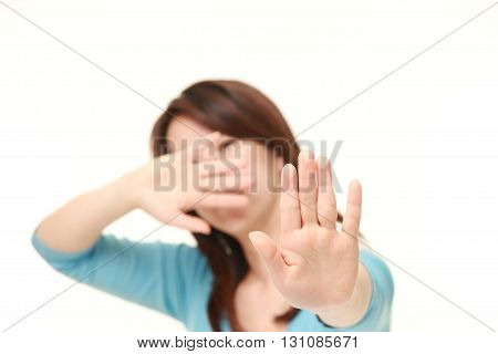 Japanese woman making stop gesture on white background