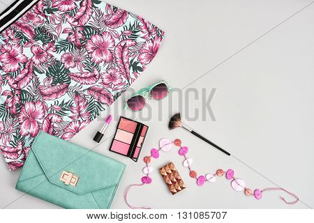 Fashion urban summer outfit, girl clothes set, cosmetics, makeup accessories. Stylish handbag clutch, trendy pink dress, necklace, sunglasses. Woman essentials. Unusual overhead, top view on gray