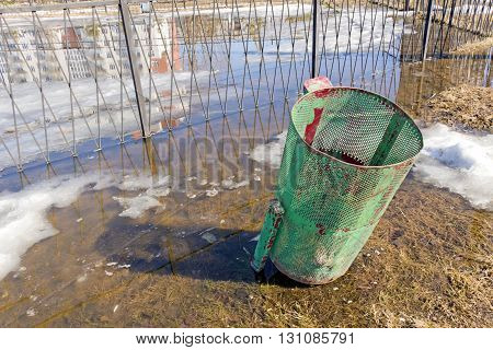 Refuse bin of red-green color in the park flooded with water from the thawing snow