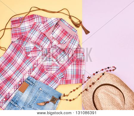 Cowboy street style Fashion girl clothes accessories set. Hipster woman, trendy plaid shirt, denim shorts, straw hat necklace. Urban country creative outfit. Overhead, top view, pink yellow background