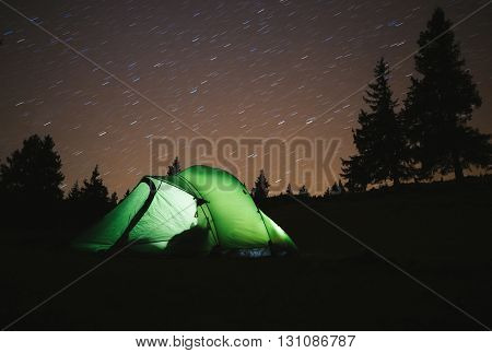 Green tent light in forest outdoor at night.