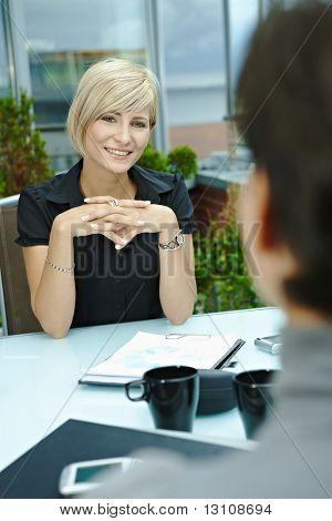 Happy young businesswoman sitting outdoor on office terrace and talking, smiling. Over the shoulder view.