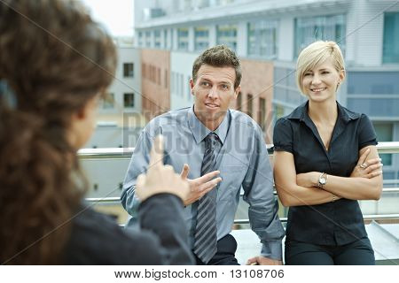 Geschäftsleute sprechen auf Terrasse des Bürogebäudes. Über die Schulter-Blick.