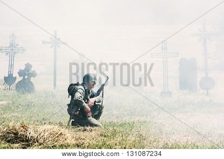 NITRA SLOVAK REPUBLIC - MAY 21: Reconstruction of the Second World War operations between Red and German army german soldier squats and patrols the cemetery on May 21 2016 in Nitra Slovak Republic.