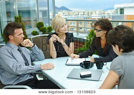 Group of young business people sitting around table on office terrace outdoor, talking and working together.