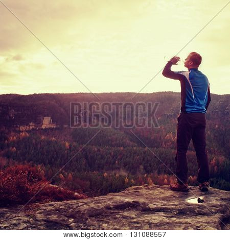 Thirsty Hiker In Blue And Black Sportswear With Bottle Of Water. Sweaty Tired Tourist On The Peak Of